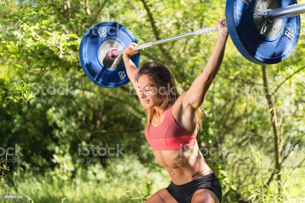 Horizontal color image of muscular woman exercising outdoors with...