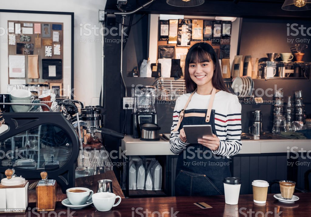 woman barista take order with tablet,asia female waitress using digital device in coffee shop business at counter bar in cafe,moder food owner business start up. stock photo