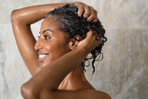 Woman bathing and washing hair stock photo