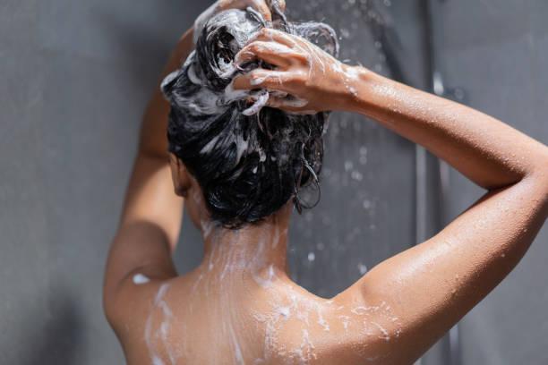 mulher tomando banho e lavando o cabelo relaxado. - shampoo - fotografias e filmes do acervo