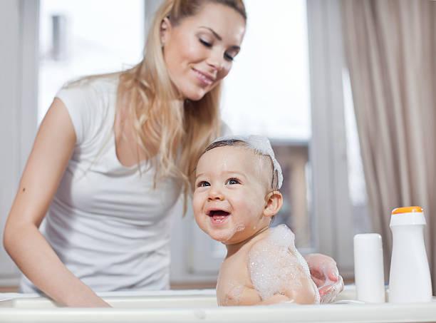 woman bathing happy baby with foam on his head and arm - baby bathtub bildbanksfoton och bilder
