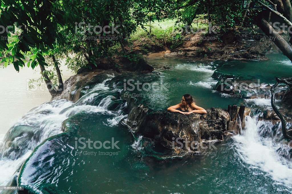 Woman bathing in hot spring waterfall stock photo