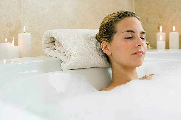 Woman bathing  bathtub stock pictures, royalty-free photos & images