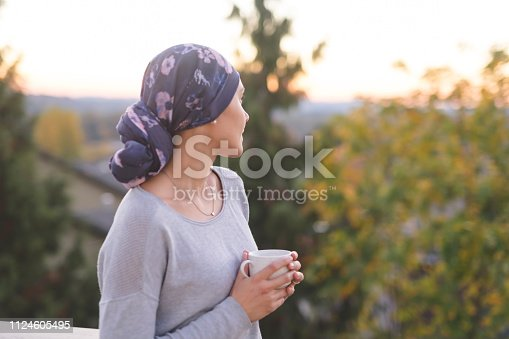 A beautiful young ethnic woman wearing a head wrap looks off in the distance and smiles contemplatively while drinking a cup of tea. She is standing outdoors and there are mountains and trees in the background.
