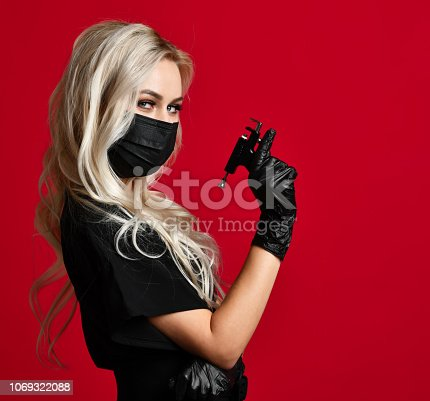 Woman beautician cosmetologist hold Ear Piercing Gun in black medical gloves and mask on red background