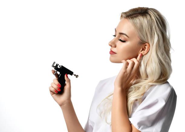 frau kosmetikerin kosmetikerin halten ohrlochpistole blick auf der ecke isoliert auf weiss - ohrringe piercing stock-fotos und bilder