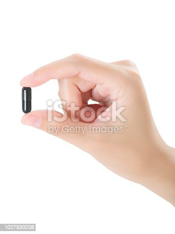 istock woman beautiful healthy hand holding medicine color black capsule, assistance concept, isolated on white background 1027530208