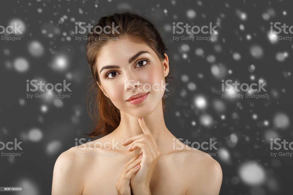 Woman beautiful, people, winter, plastic surgery and beauty concept - beautiful young woman face over blue background and snow stock photo