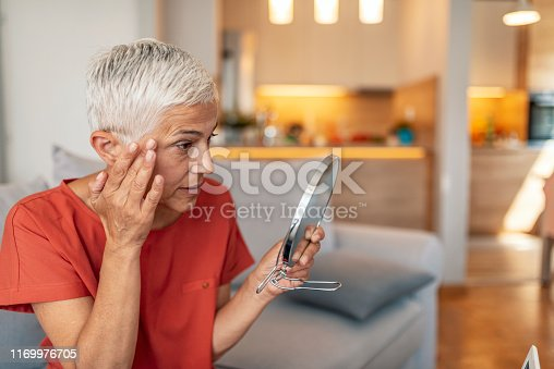 Photo of Attractive senior woman looking at her skin in the mirror. Beautiful senior woman in front of the mirror at home during the day.