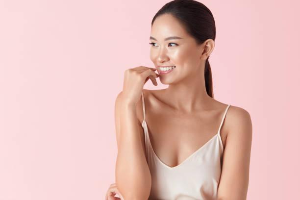 frau. schönheit asiatischen modell portrait. lächelnde weibliche berührt gesicht und wegschauen. schöne ethnische mädchen mit gesunden glatten haut und nackt make-up vor rosa hintergrund. - asien stock-fotos und bilder