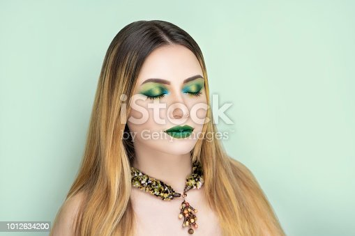 Close-up portrait of beautiful girl woman pretty lady, professional makeup, long hair styling ombre. Luxury new green color make-up shiny lipstick lip-gloss glossy cosmetics. art photo conceptual idea