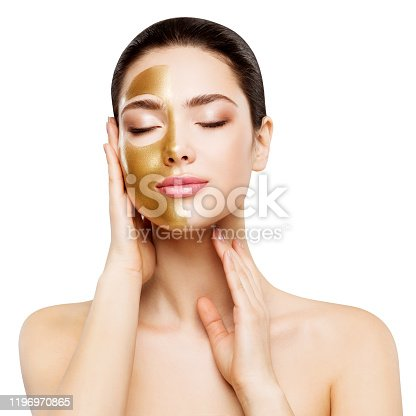 Woman Beauty Gold Mask , Beautiful Girl applying Golden Skin Cosmetic to Face, Isolated over white background