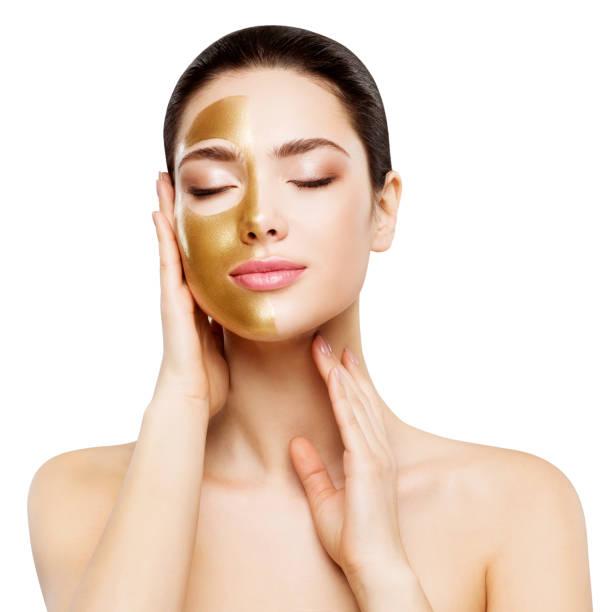 Woman Beauty Gold Mask , Beautiful Girl applying Golden Skin Cosmetic to Face stock photo