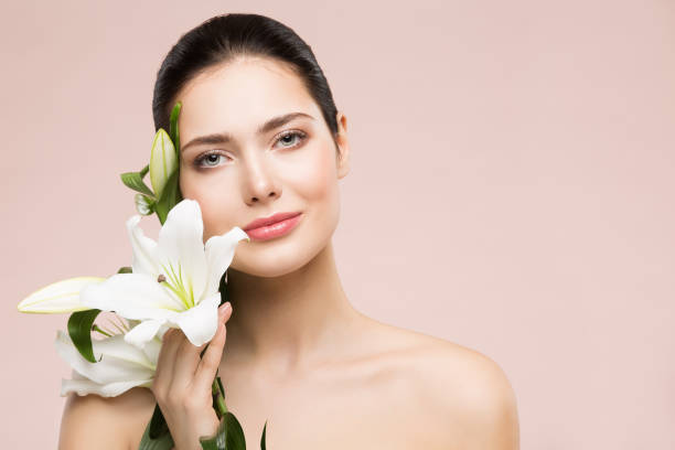 Woman Beauty Natural Makeup Portrait with Lily Flower, Happy Girl Face Skin Care and Treatment stock photo