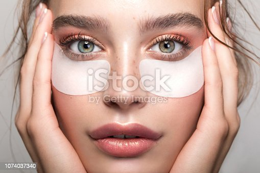 Closeup studio shot of a beautiful young woman with freckles skin and under eye mask posing against a grey background