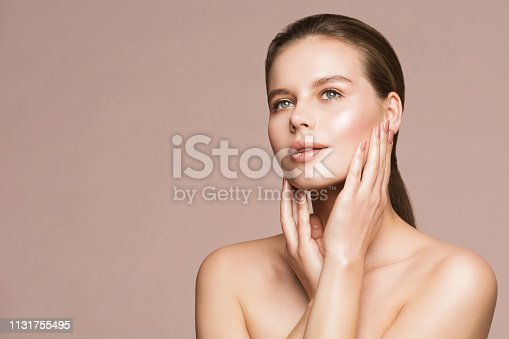 Woman Beauty Portrait, Model Touching Face, Beautiful Girl Makeup and Nails Treatment over beige studio background