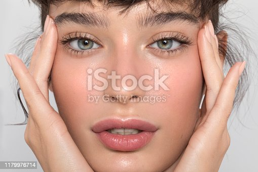 Close up studio shot of a beautiful woman with perfect skin, she touching her face