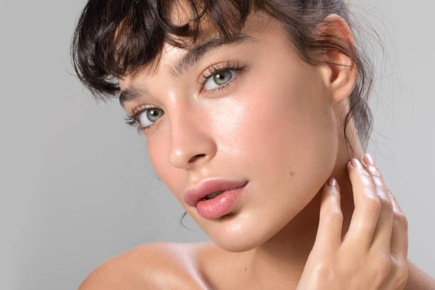 Woman beauty portrait Close up studio shot of a beautiful woman with perfect skin, she touching her face glowing stock pictures, royalty-free photos & images