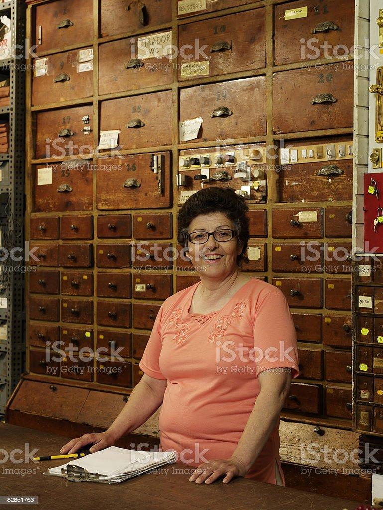 Woman behind counter at hardware store royalty free stockfoto