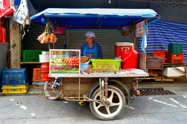 Woman behind her street food push cart in Phuket Town stock photo