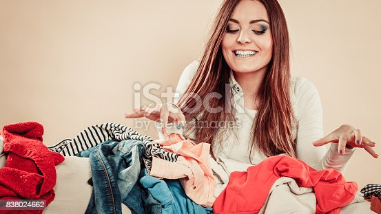 460589747 istock photo Woman behind sofa full of clothes with lifted hands. 838024662