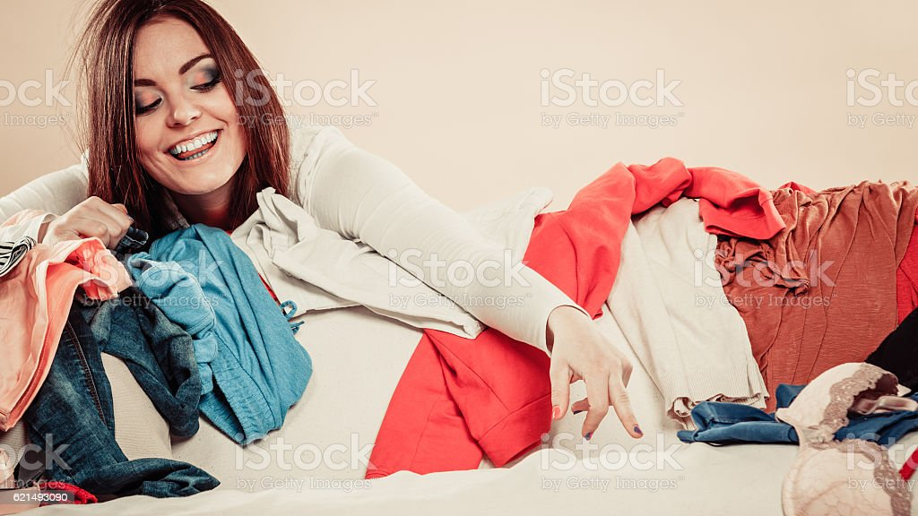 Woman behind sofa full of clothes with stretched arm. Lizenzfreies stock-foto
