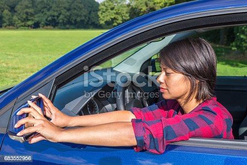 istock Woman behind steering wheel adjusting car mirror 683552956