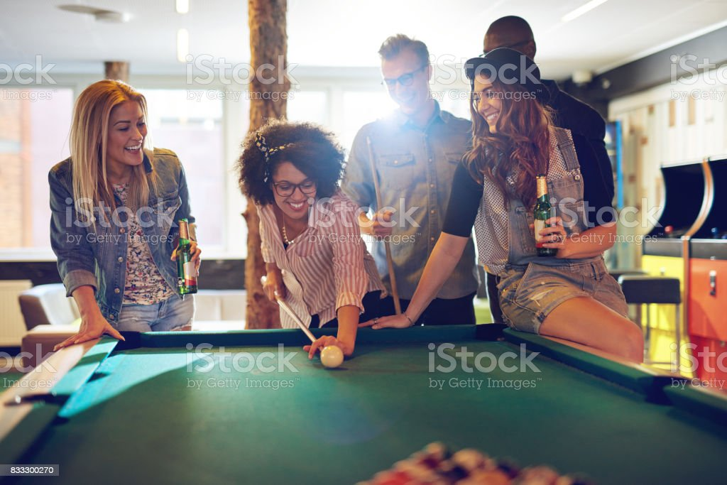 Woman behind the cue ball while friends watch stock photo