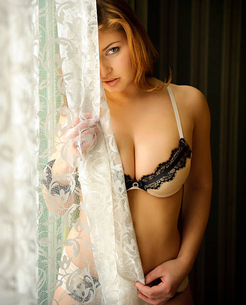 Woman behind the curtain stock photo