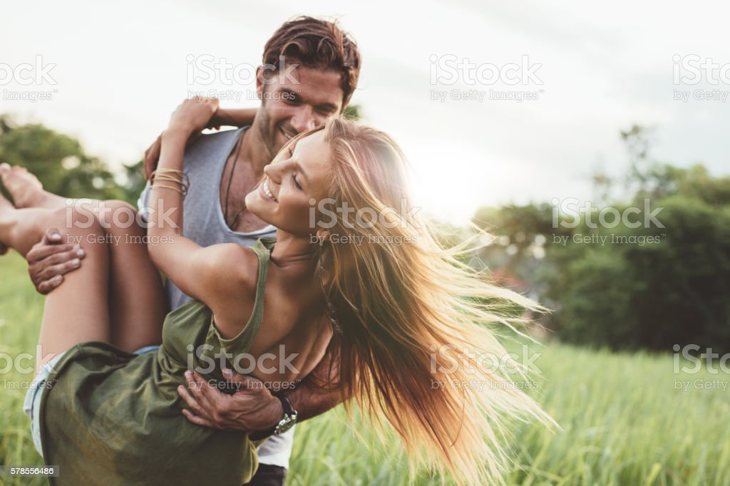Woman being carried by her boyfriend in field stock photo