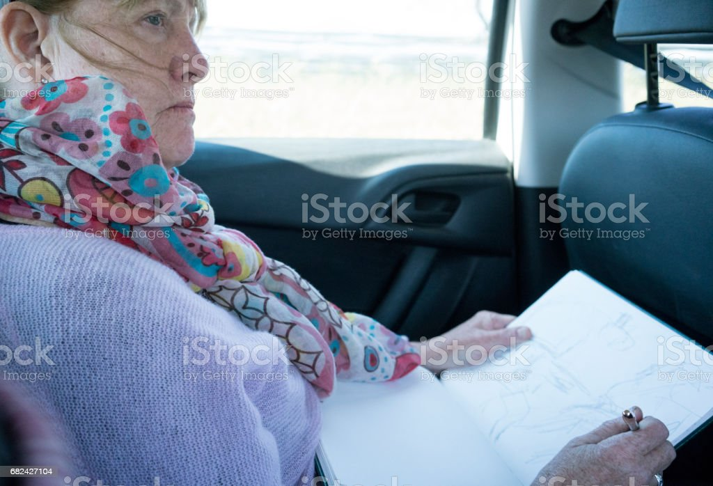 Woman being creative, sketching from the back seat of a car royalty-free stock photo