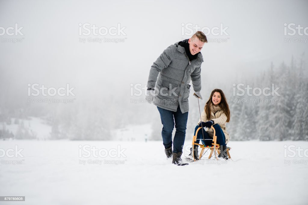 Woman being dragged on sledge by her boyfriend stock photo