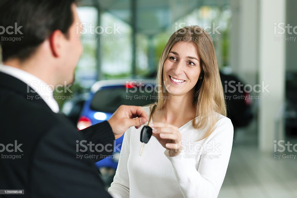 Woman being handed the key to a car she purchased royalty-free stock photo