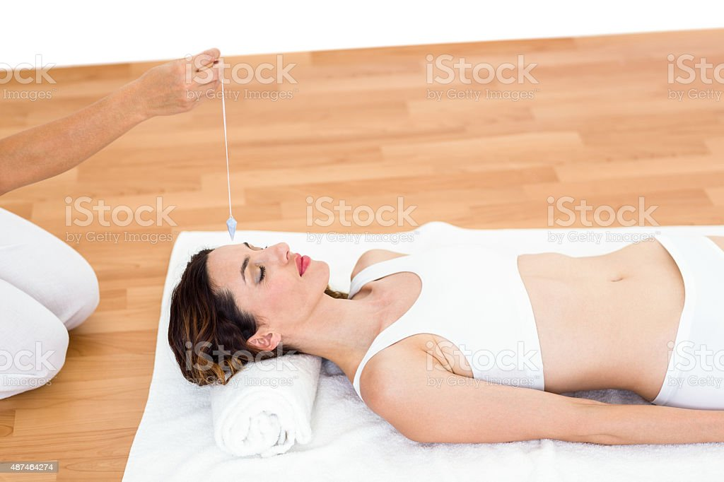 Woman being hypnotized while lying on the floor stock photo