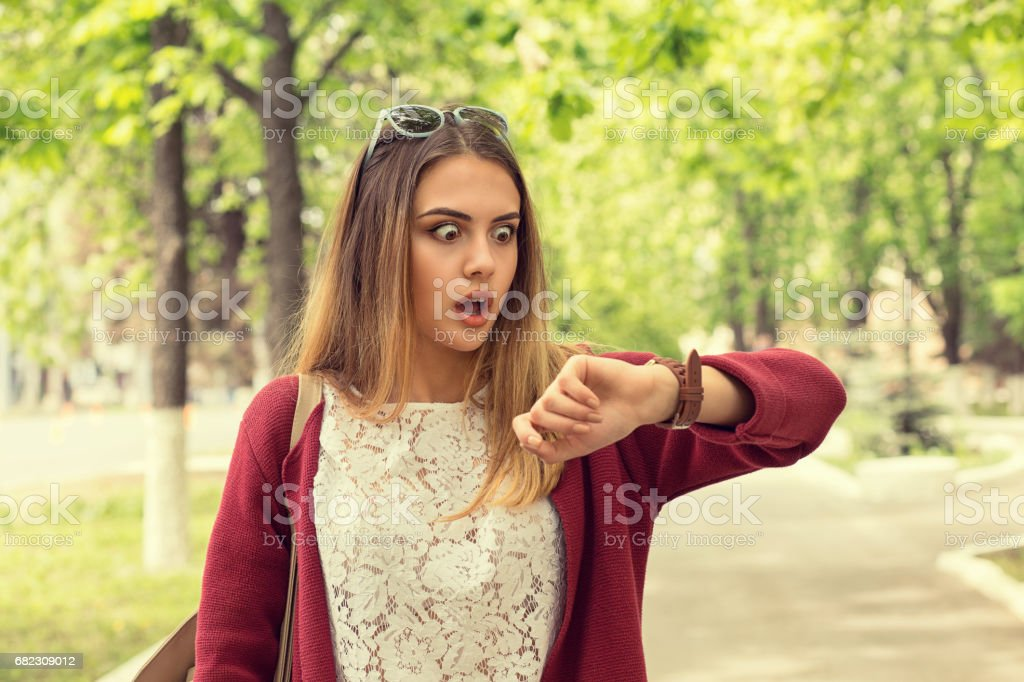Woman being late to a rendez-vous. Closeup portrait headshot view stressed young attractive beautiful businesswoman checking the time outdoor isolated park cityscape outdoor background. Mixt race girl stock photo