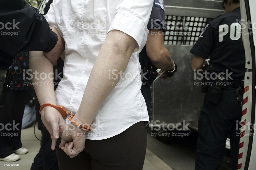 A woman being placed under arrest stock photo
