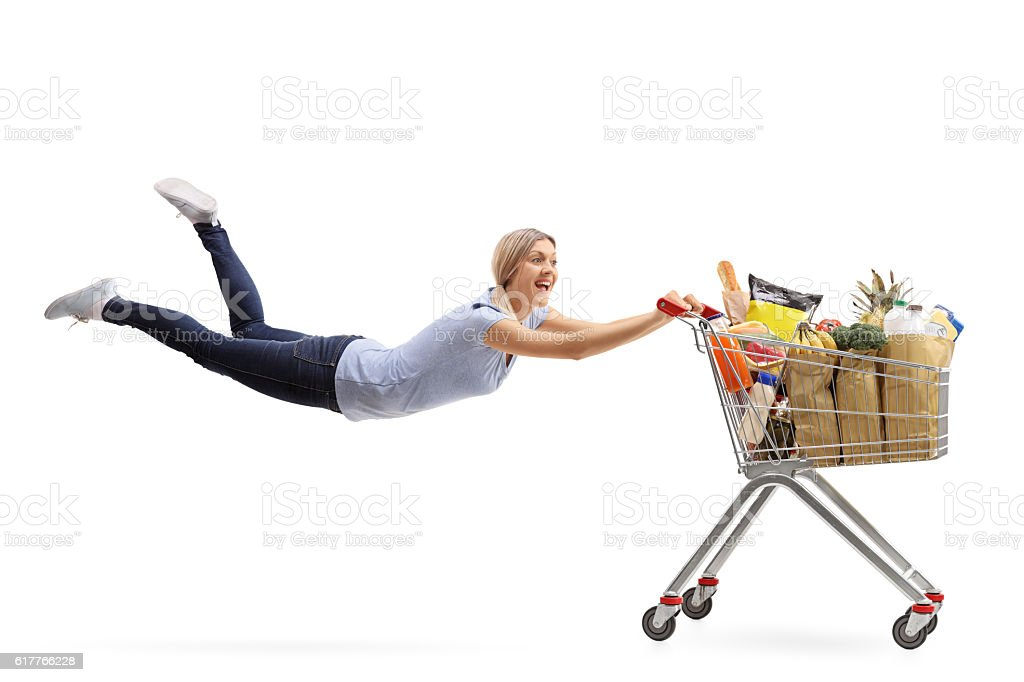 Woman being pulled by a shopping cart stock photo