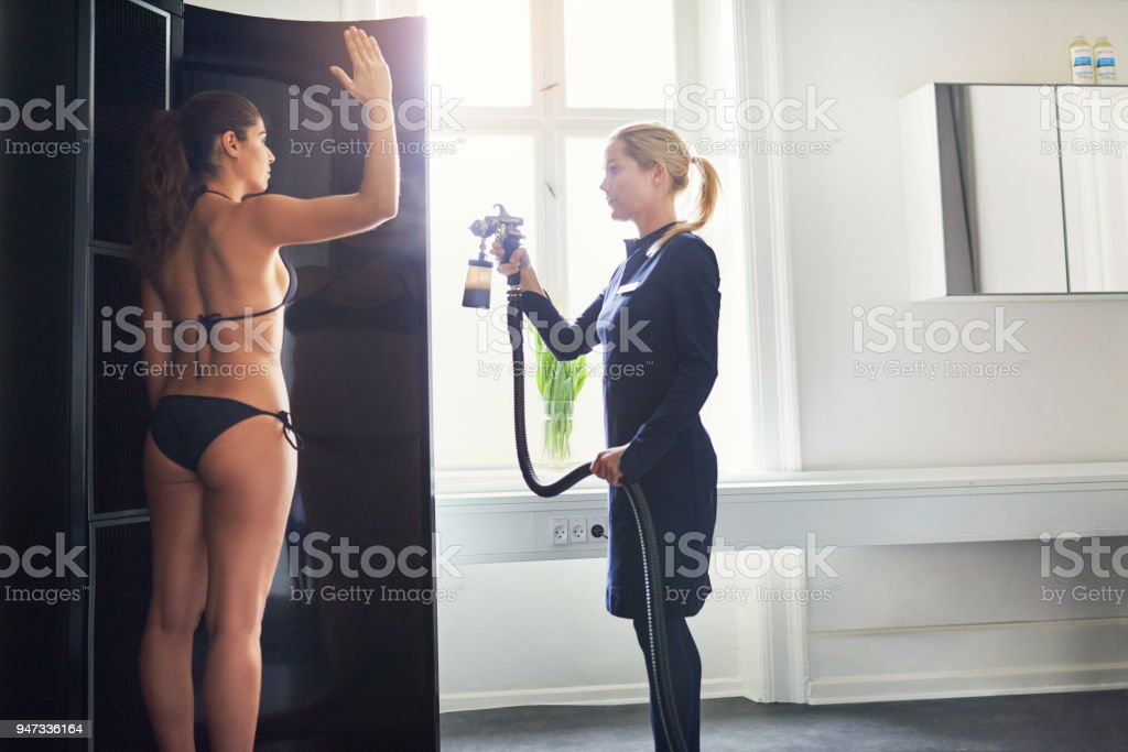 Woman being sprayed with bodypaint during spraytan session stock photo