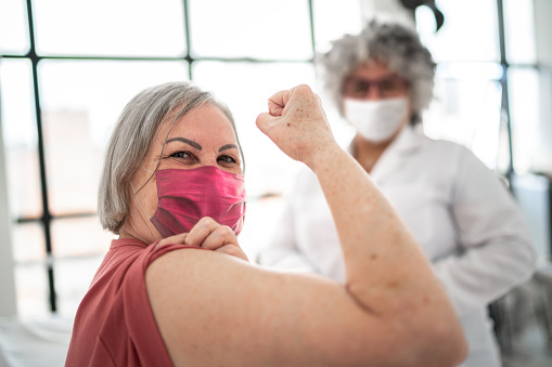 Woman being vaccinated and flexing biceps muscle - wearing face mask