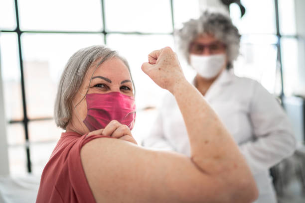 Woman being vaccinated and flexing biceps muscle - wearing face mask stock photo