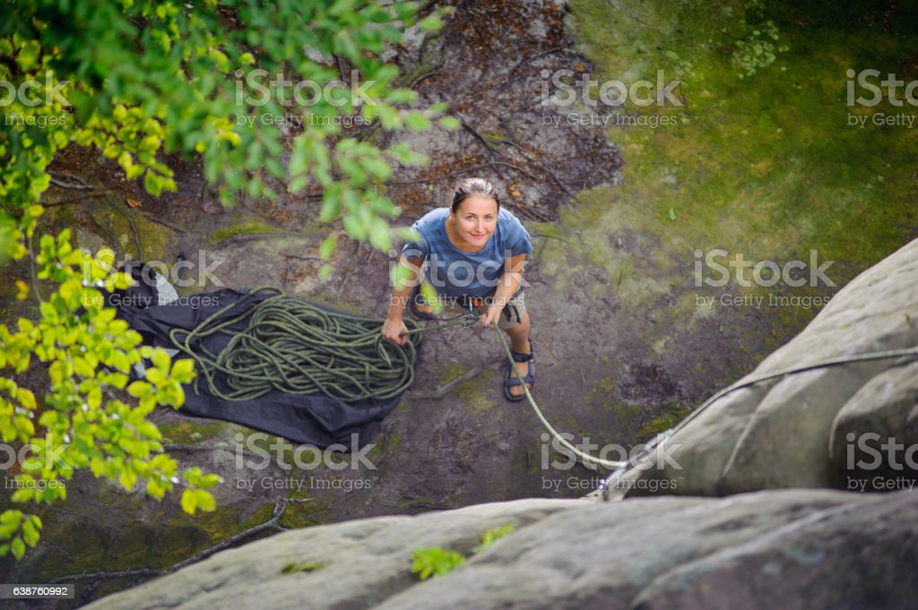 Woman belaying another climber with rope stock photo