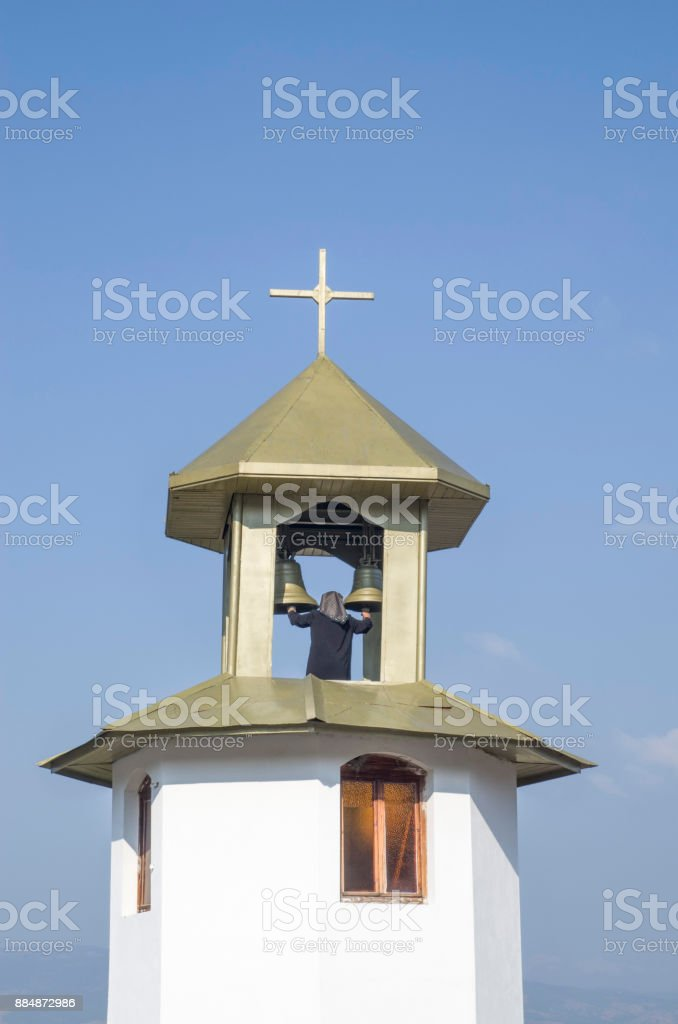 Woman bell-ringer in orthodoxy church bell tower, Bulgaria stock photo