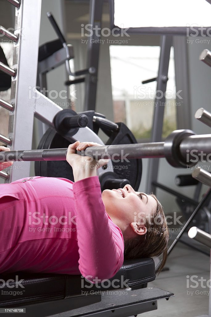 Woman Bench Pressing Weights at Health Club royalty-free stock photo