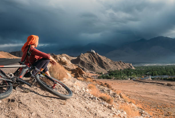 Woman bicycle traveler Woman bicycle traveler looking to Ladakh mountain range, India female biker resting stock pictures, royalty-free photos & images