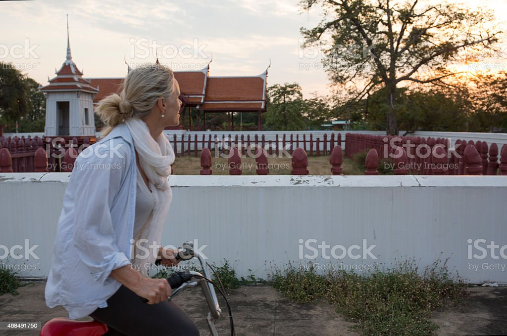 Woman bicycles past Thai temple at sunrise stock photo