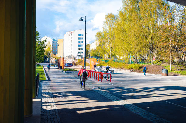 A woman bicyclist riding with her children on a bicycle lane at downtown Helsinki stock photo