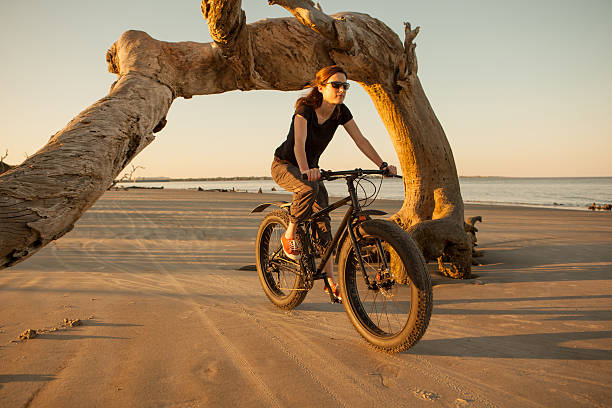 A woman biking late in the afternoon along the beach  stock photo
