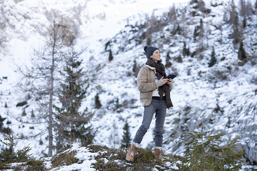 Woman biologist in the winter wild with mobile phone