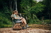 One woman, lady explorer and biologist taking notes in nature by waterfall alone.