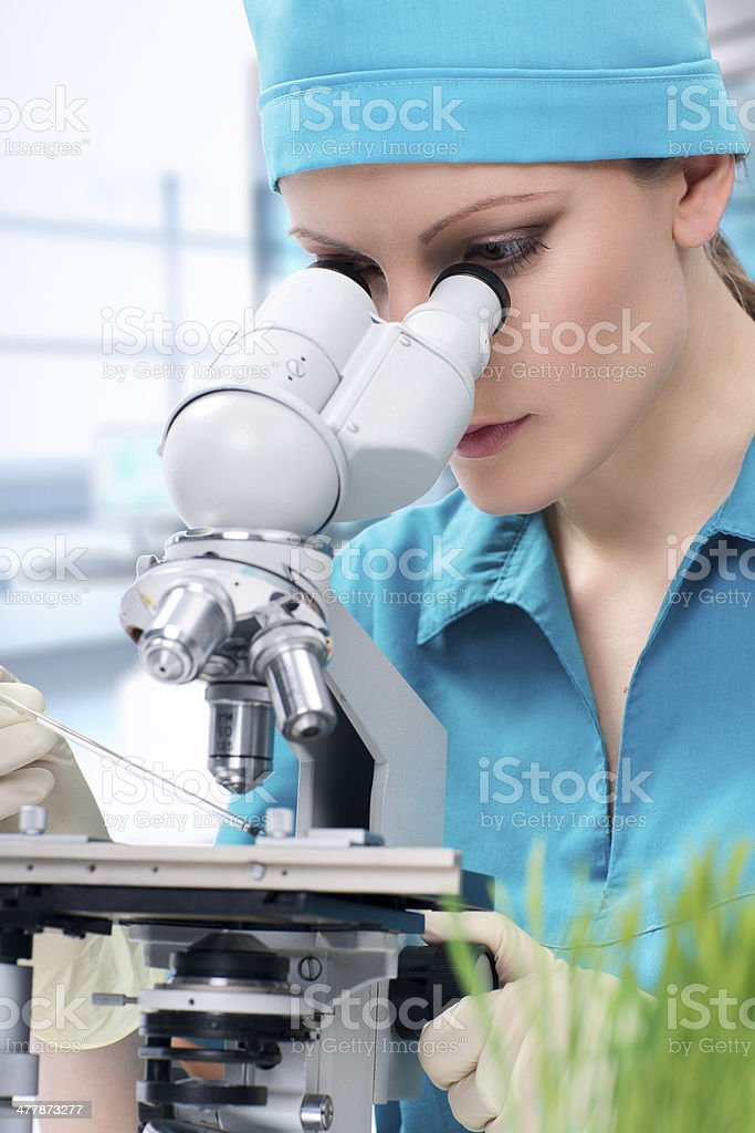 Woman biologist working with microscope royalty-free stock photo